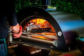 Pizza in oven being collected.jpg