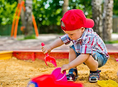 Toddler playing in sand box. Childcare near me. Daycare near me.