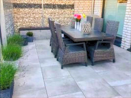 Keramikplatten Terrasse mit Sitzmauer und Gabione. Tisch in Mitte und Lavendel in Pflanztöpfen