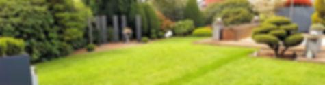 Schöner grüner Garten mit Fertigrasen und vielen Pflanzen. Holzdeck mit Pool im Hintergrund.