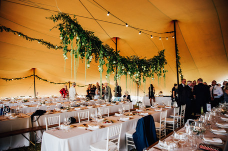 Hanging wedding garland in pole tent.