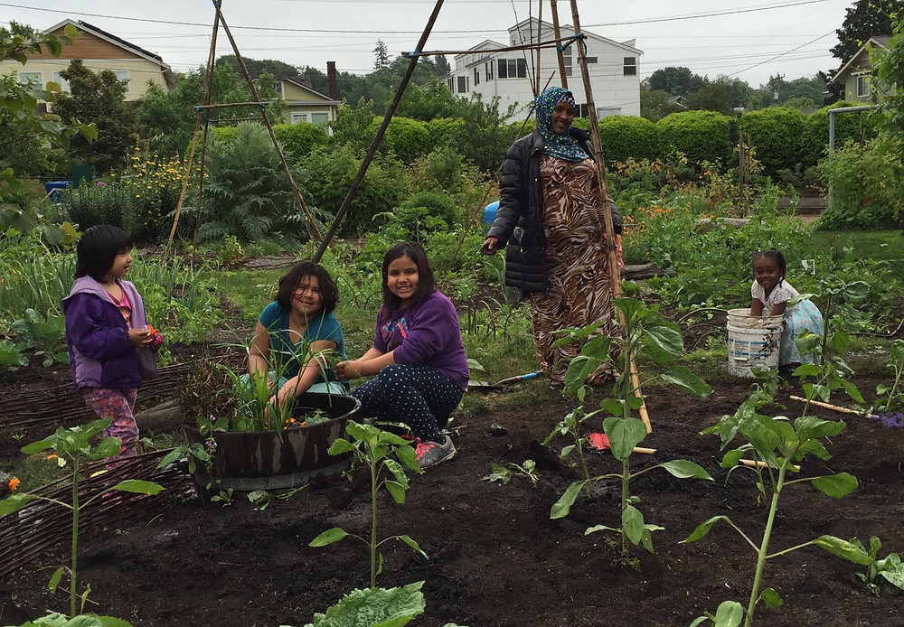 4 Girls and their Mother-Caretaker working in the garden