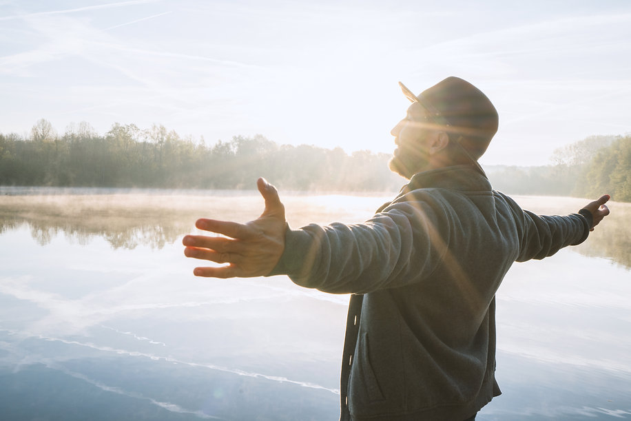 Young man arms outstretched by the lake