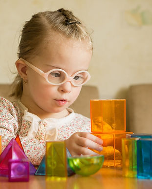 Girl with Down syndrome playing with geometrical shapes.jpg