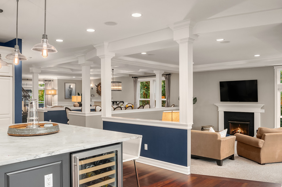 Kitchen island with wine fridge and view into the great room