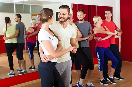 Group of smiling russian people dancing salsa in studio