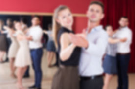 Adult dancing couples enjoying foxtrot in dance studio