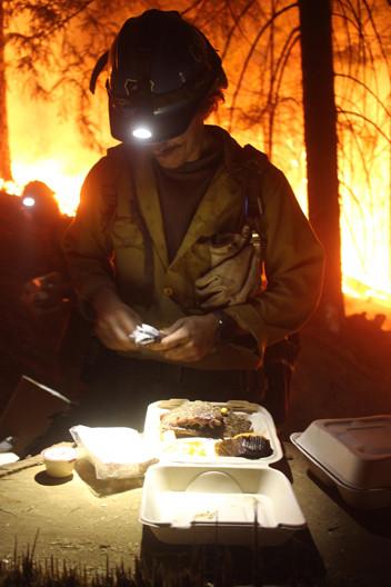 wildland firefighters engine crew member eats dinner on the fireline