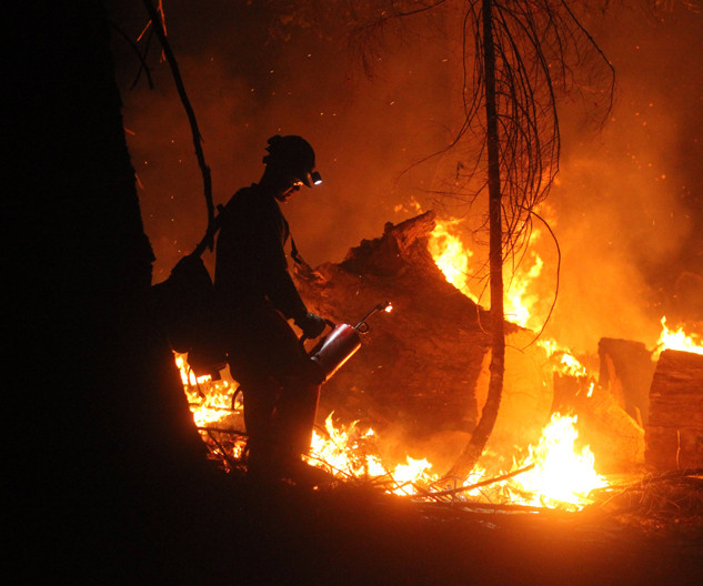 wildland firefighter hotshot crew member conducts firing operation with drip torch