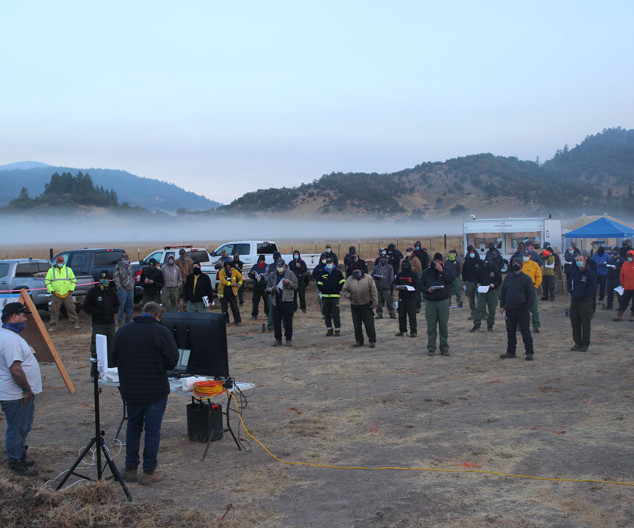 wildland firefighter operations briefing at Hettenshaw fire camp