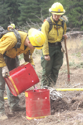 wildland firefighter engine crew members refill fuel can