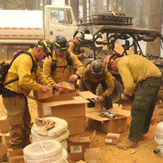 wildland firefighters gather firefighting equipment - hose and supplies