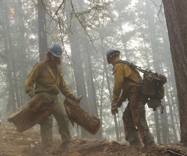 wildland firefighter hotshot crews move heavy fuels from fireline
