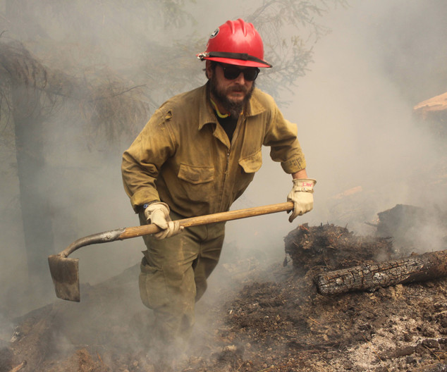 wildland firefighters engine crew member mops up hotspots with a hand tool