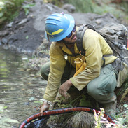 wildland firefighter engine crew member tends to fire hose and pump on the fireline