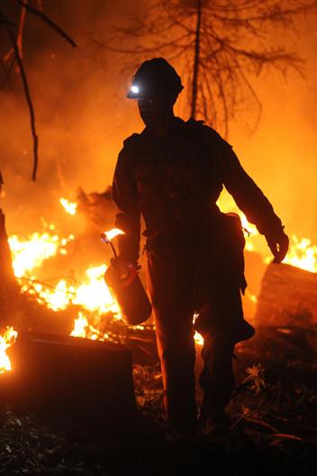 wildland firefighter hotshot crew member uses a drip torch