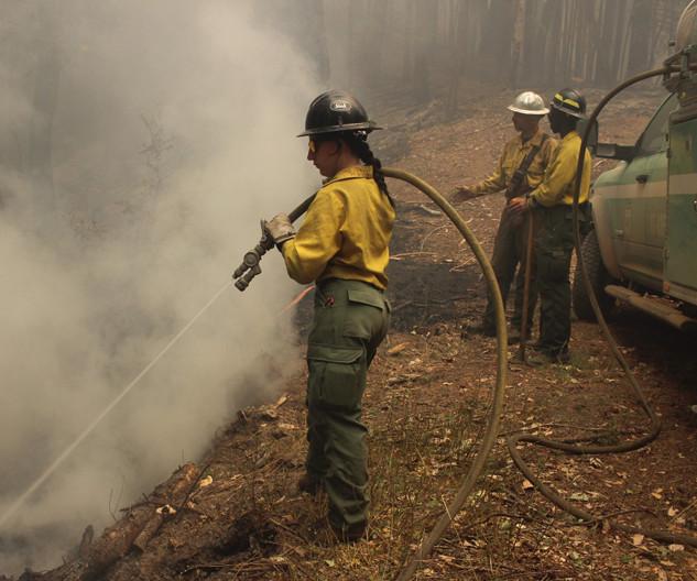 wildland firefighter engine crew member sprays fire with hose
