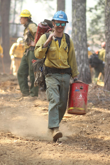 wildland firefighters hotshot crew members hike the fireline with heavy equipment