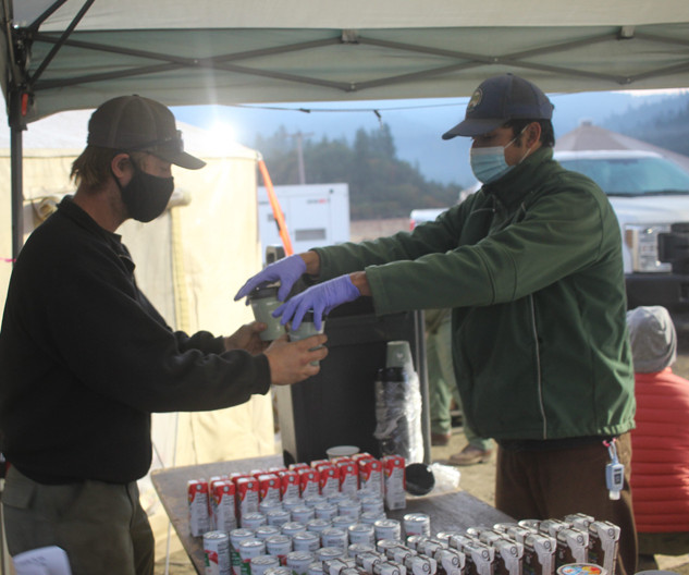fire camp crewmember serves wildland firefighters coffee in fire camp