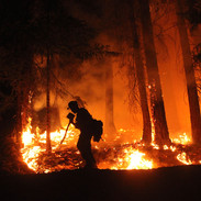 wildland firefighters hotshot crew member hikes the fireline at night