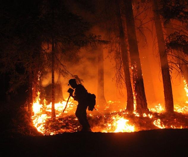wildland firefighters hotshot crew member hikes the fireline at night