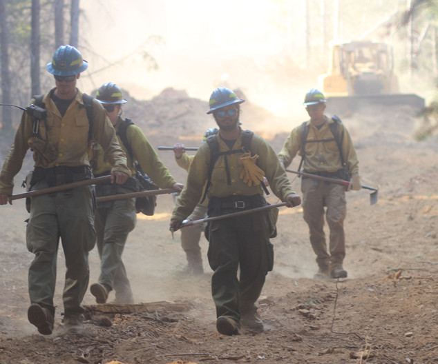 wildland firefighters engine crew members hike the fireline