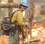 wildland firefighter hotshot crew member holds the fireline during firing operation