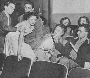 Caption: 'Don't be late and make like monkeys, over legs, and laps to climb, ruining nylons and the fun of all the folks who came on time!'