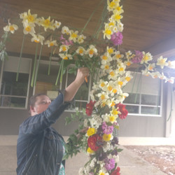 Pastor Rebecca Patterson placing her flowers on the Easter Flower Cross - 2021