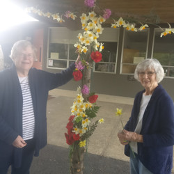 Jeannie Chapin placing flowers on Easter Flower Cross - 2021