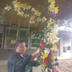 """Pastor Rebecca Patterson """"tiding up"""" the Easter Flower Cross - 2021"""