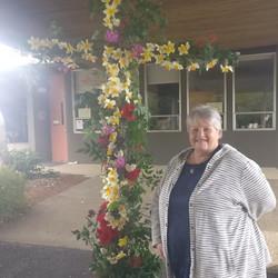 Nancy Adams placing flowers on Easter Flower Cross - 2021