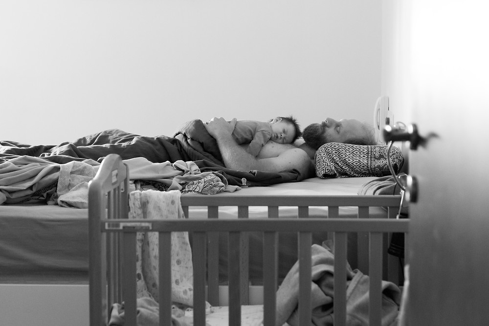 Dad lying on bed with baby lying on top of his chest