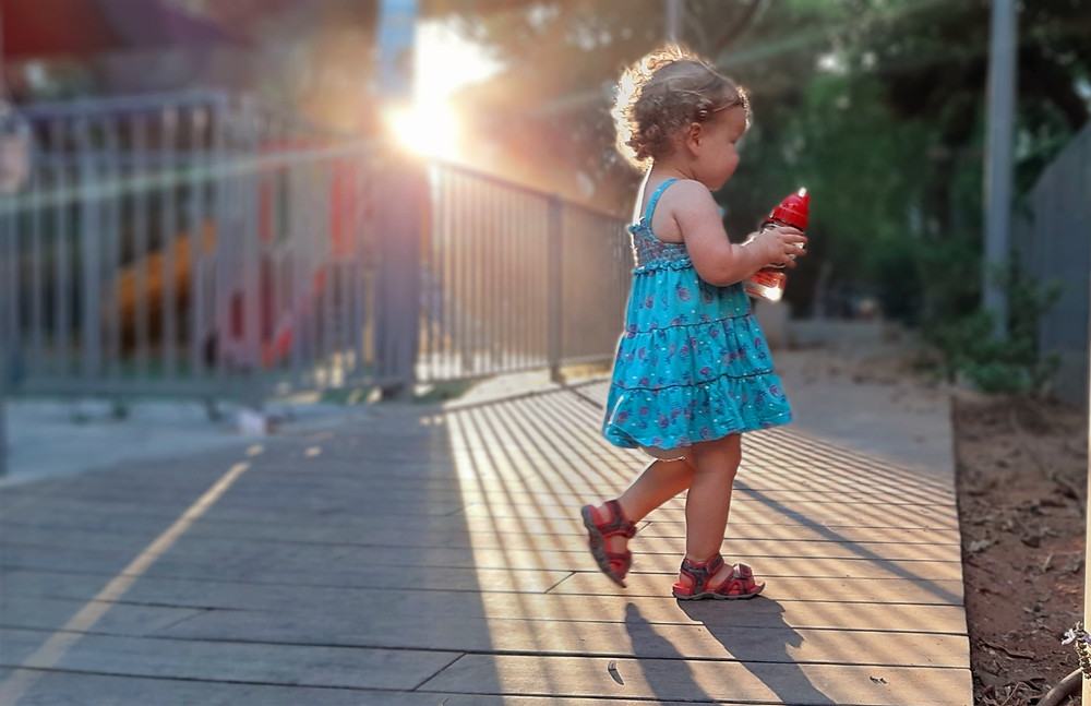 Toddler walking in sun light and shadow holding a water bottle