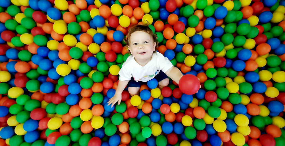Child holding red ball in ball pit