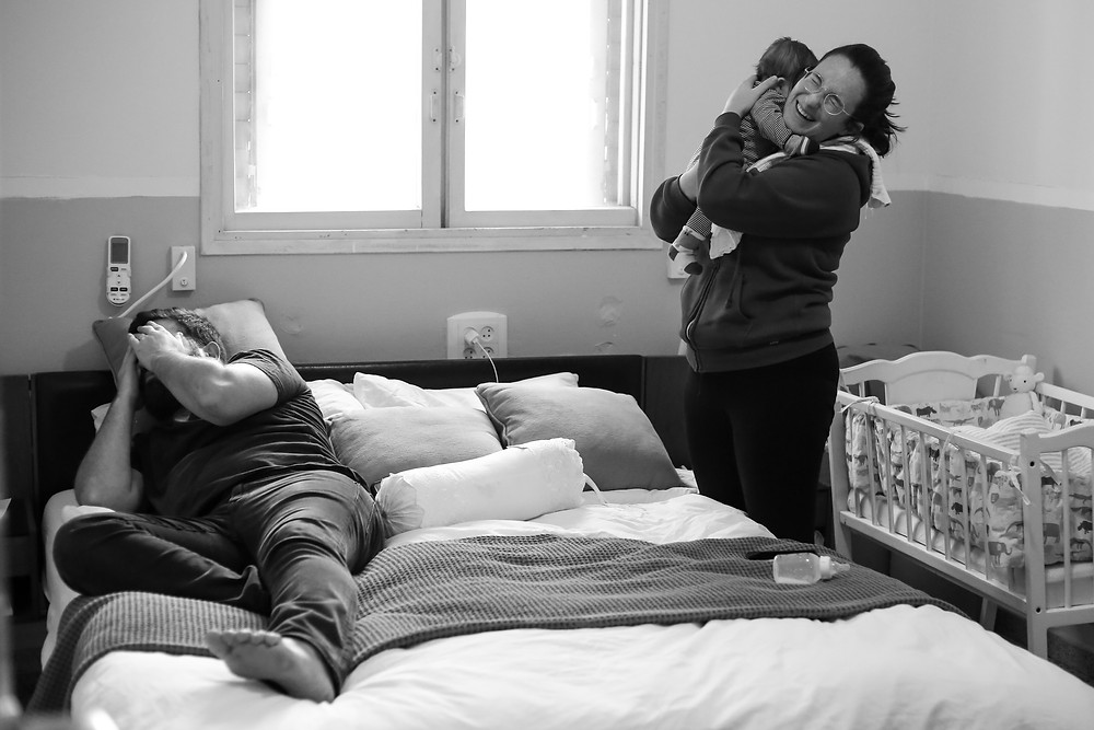Dad lying on bed, mom holding baby