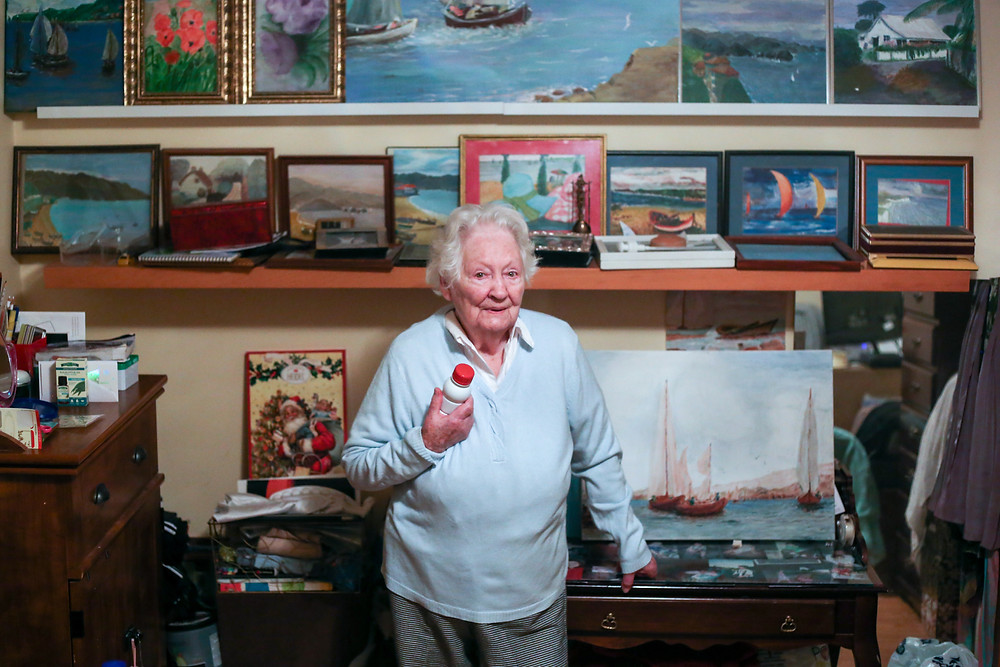 portrait of a 93 year old woman with paintings behind her