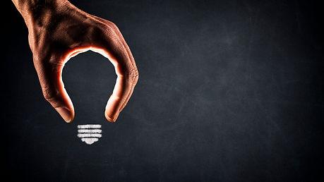human-hand-light-bulb-on-blackboard-new-