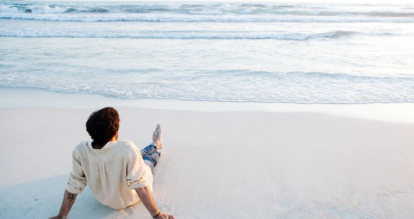 Man sitting on beach gazing out at ocean