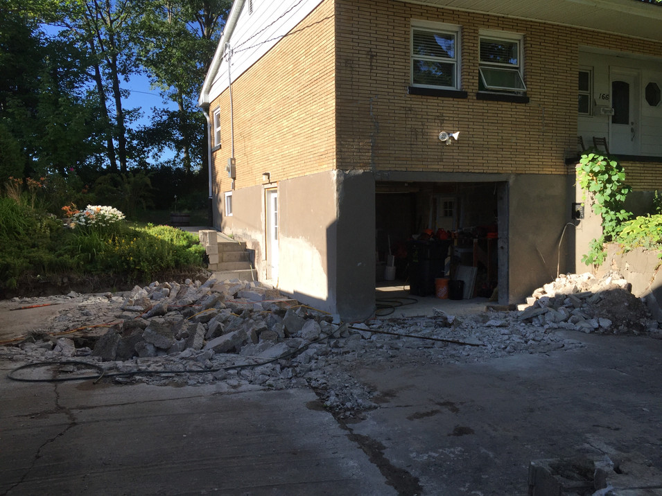 The concrete on the driveway and retaining walls was so cracked and damaged it all needed to be removed. The garage door had been framed in and closed up, we turned it back into a functional door.