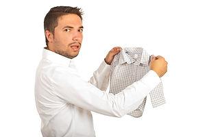 Shocked man holding shrunk shirt and loo