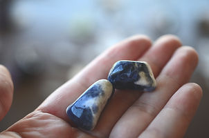 Woman's hand holding blue healing crysta