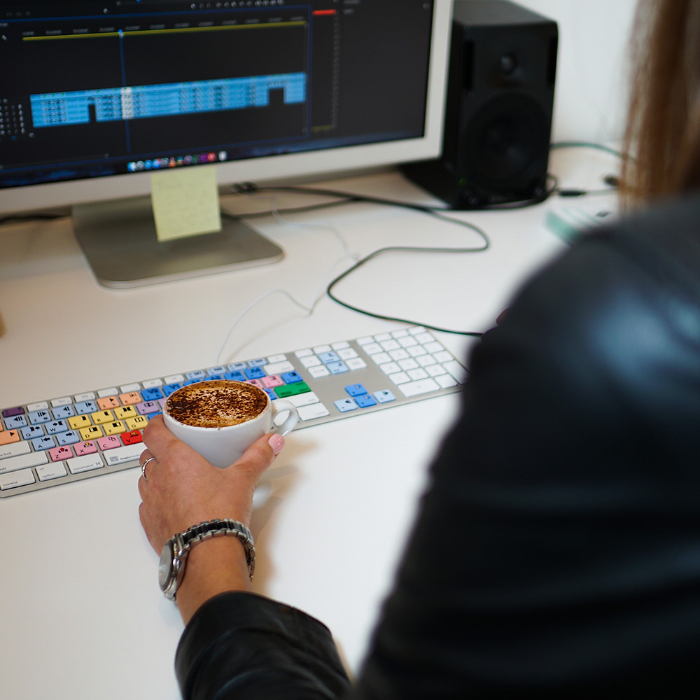 Young woman editing video material with coffee in hand