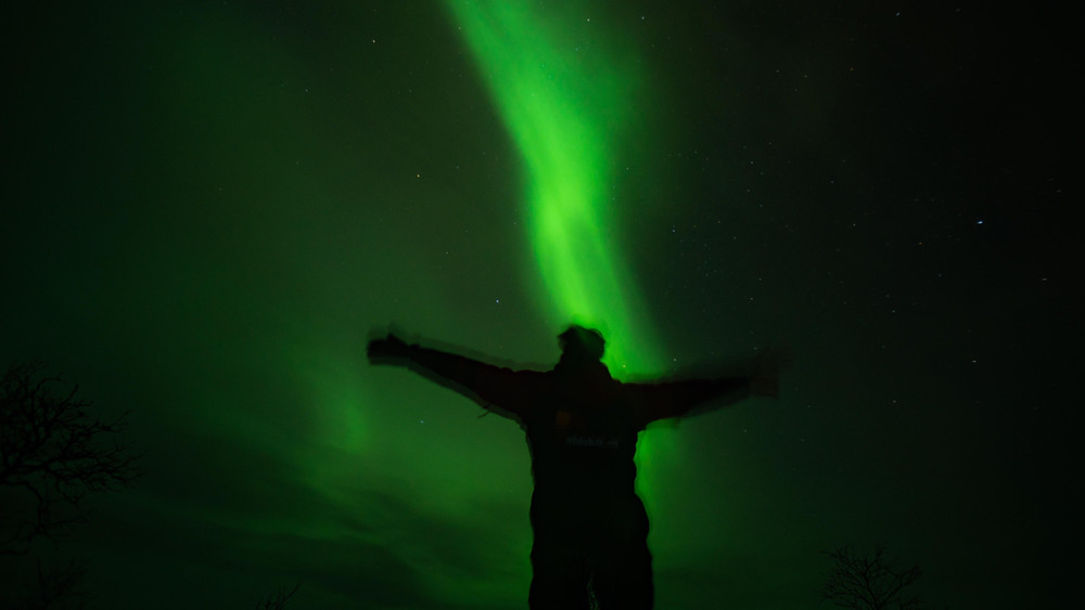 Man observing Aurora Borealis - Northern Lights, holding arms in triumphant position, Abisko, Sweden.