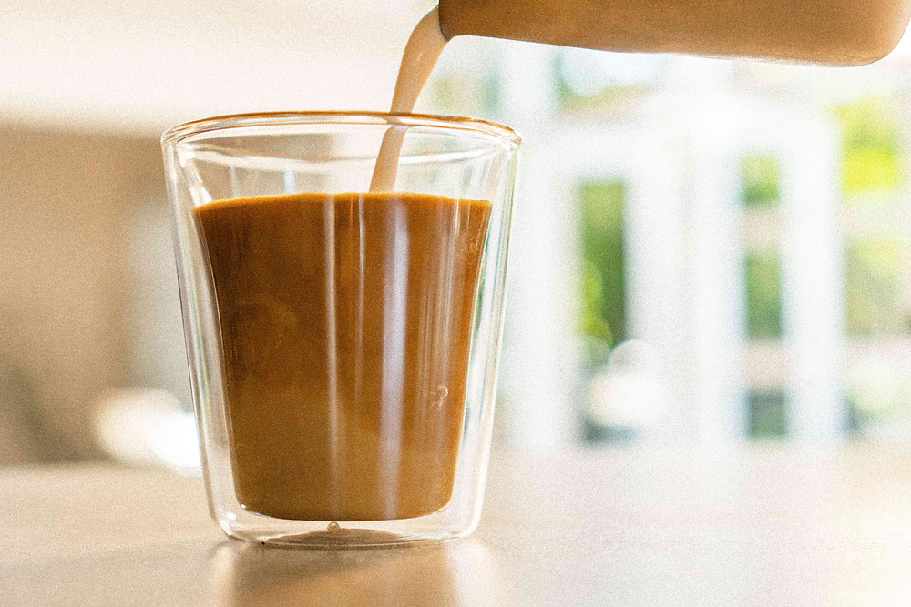 Iced latte milk jug pouring into double walled glass with espresso