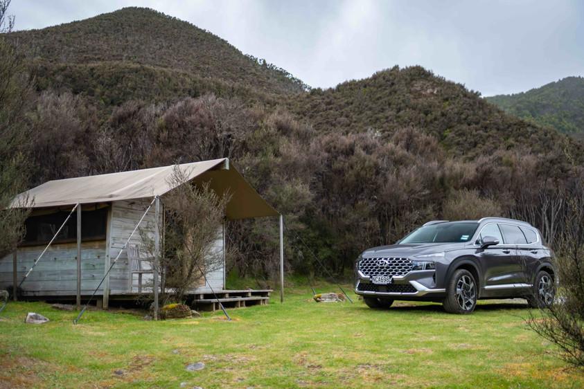 Hyundai Santa Fe next to camping hut