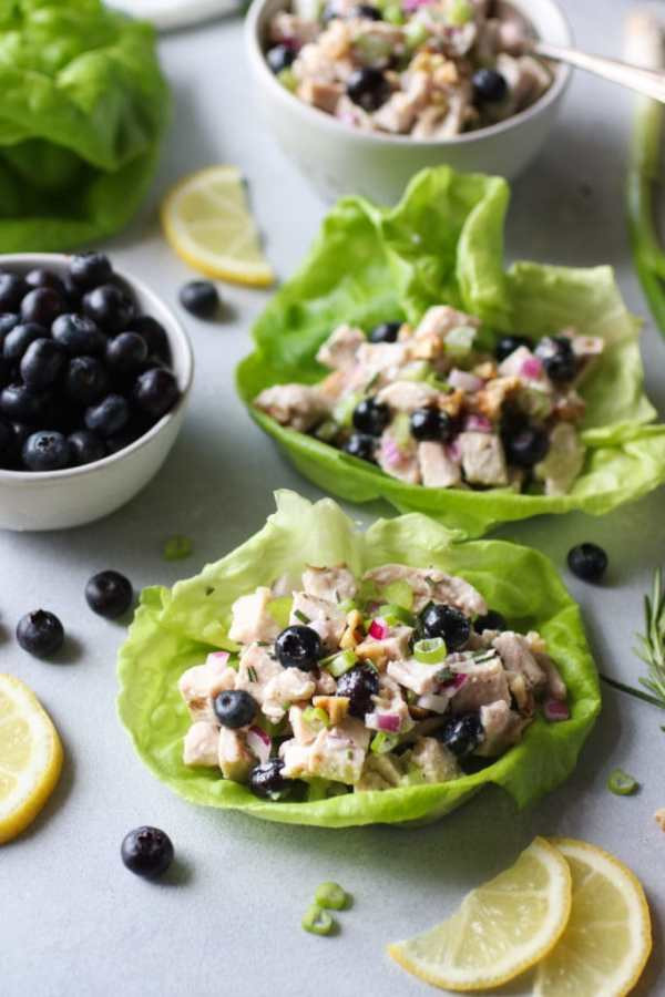 Chicken salad nestled in a lettuce leaves with blueberries. Bowl of blueberries and lemon slices on the side.