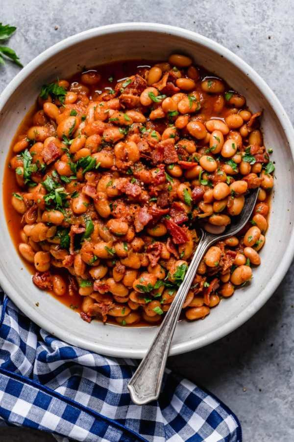 Bowl of baked beans with bacon chunks and herb garnish with a spoon dipped in it and blue-checker napkin around it