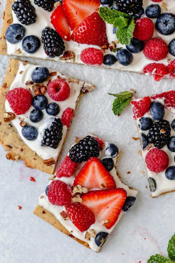 Overhead photo of Gluten-free Berry Fruit Pizza garnished with a sprig of mint in the center. Crust is topped with Greek yogurt and topped with an assortment of berries. Picture shows a bite taken out of one of the squares.