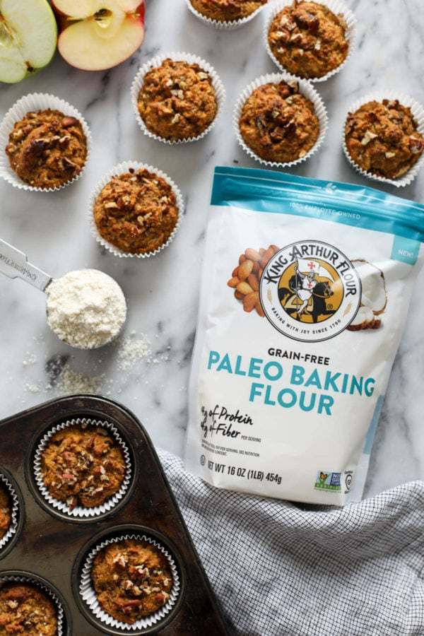A bag of King Arthur Flour lying on a marble countertop surrounded by Paleo Morning Glory Muffins and a scoop of flour.